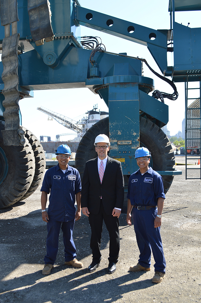 Left to Right (in front of the world's third largest Marine Travelift): Don Ramos, Welder, Great Lakes Shipyard; Thomas Perez, U.S. Secretary of Labor; Darwin Ramos, Welder, Great Lakes Shipyard. Both Don and Darwin participated in the Great Lakes Shipyard internship program and were hired as full-time employees.